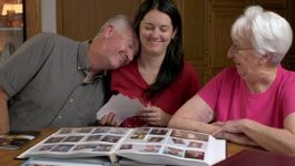 Tegan Griffiths looks at photo album with parents. American Creed film still.