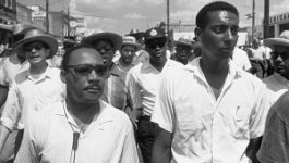 Dr. Martin Luther King, Jr. and Stokely Carmichael march with a crowd of people behind them.