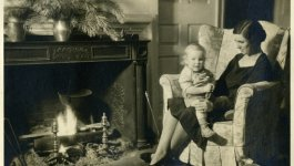 Martha Sharp holds a baby on her knee while sitting in an armchair in front of a fireplace.