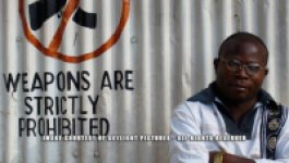 """A Congolese man stands next to a white wall of corrugated metal that has a """"no weapons"""" sign consisting of an image of an automatic weapon with a red X."""