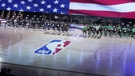 NBA players and staff kneel court-side.