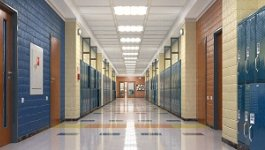 An empty school hallway with yellow walls and blue lockers.