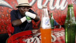 A man and a child sit at a table in a restaurant. The man takes a drink from a can using his residual limbs.