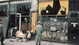 photo of storefronts with broken windows following Kristallnacht