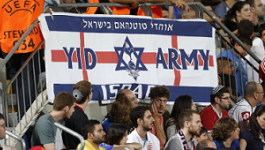"Fans in a soccer stadium with a banner depicting a star of David and words ""Yid Army."""
