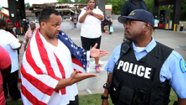 Man with an American flag wrapped over his shoulders talking with a police officer.