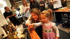 Young woman and little girl light a candle at Passover. Teaser image for reading on Being Jewish in the United States.