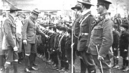 World War I officers in uniform with a group of boy scouts standing in line formation.