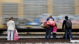 People wait along train tracks as a freight train rushes by.