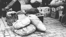 A group of people stand and sit on a cobblestone street around piles of luggage and large sacks of belongings.