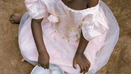 A black African girl in a pink dress looks up at the camera with a bowl in her hand.