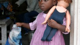 A black African girl in a pink dress stands in a doorway, hugging a doll and waving a cloth.