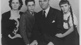 A family of four poses for a portrait. The man and boy wear suits, while the woman and girl wear dresses. Taken approximately in the 1950s.