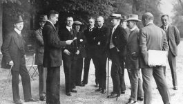 Several German delegates stand in a group, while one reads a document.