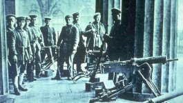 Approximately 10 German soldiers stand between large structural columns, next to several machine guns. Circa 1918.