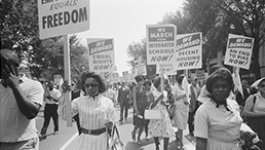photo of people on a march with signs that advocate for school integration