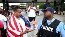 Photo of a police officer talking to a man with an American flag on his shoulders