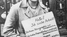 A young unemployed woman stands on the sidewalk wearing a hat, coat, and a sign around her body stating her job skills.