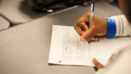 Student's hands writing on lined paper.