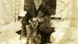 Waitstill Sharp sits on the stoop in winter with a dog. Circa late 1930s.