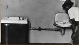 "Two water fountains against a wall, one labeled ""White"" and the other labeled ""Colored."" An African American person drinks from the ""Colored"" fountain."