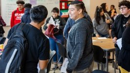 Student smiling at a peer with students moving with backpacks around them.