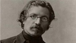 Profile of playwright Sholem Aleichem seated wearing glasses.