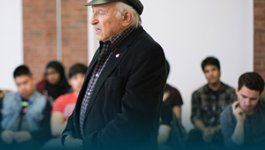 A Holocaust survivor stands speaking in the foreground. Students are seated in the background.