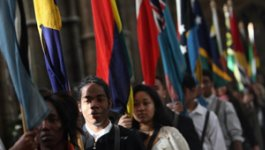 Line of young men and women each holding flags from different countries.
