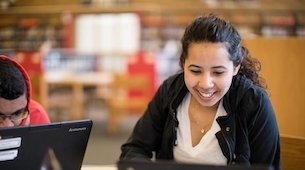 Female student smiling and looking at a laptop computer