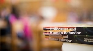 Holocaust and Human Behavior Books in the foreground with blurred background.