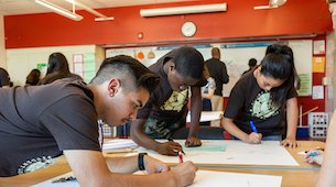 Three students taking part in a big paper activity