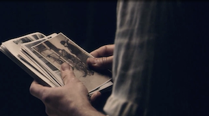 Close up of someone looking at images from Jewish life before the Holocaust.