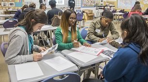Four students sitting around a table writing on handouts.