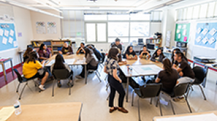 A wide view of a bright classroom with two tables filled with students and an educator standing in the middle.