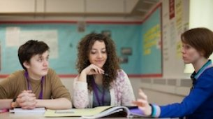 Image of a female student and a male student listening to a female teacher.