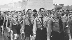image of men walking with man in front staring into the camera