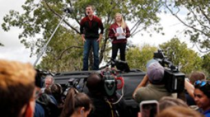 image of two students speaking to the media during a protest