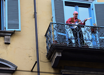 A man plays his guitar on a balcony.