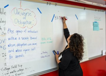 A teacher writes on a large piece of paper taped to a classroom whiteboard.