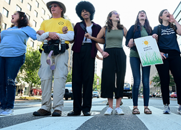 Demonstrators stand in a crosswalk to protest climate change.