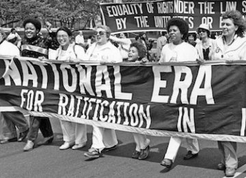 """Women hold a banner reading """"National ERA"""" in a march outdoors."""