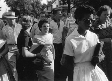 historical photograph of Elizabeth Eckford in white dress and sunglasses walking into Little Rock school surrounded by a crowd.