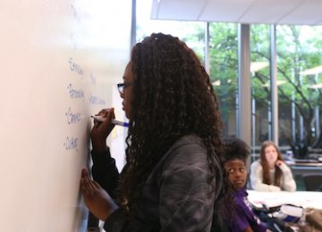 A young woman writes on a classroom wall.