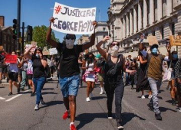A crowd wearing masks marches during a May 2020 protest against the police killing of George Floyd.