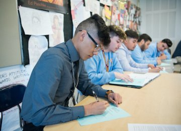 Students sit at their desks writing in journals.