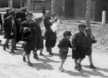 Young children and women walk beside fence.
