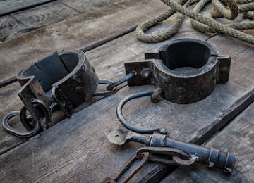 Rope and meta shackles on a distressed wooden floor.