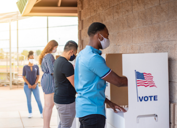 A group of people wearing masks while voting in the 2020 US election.