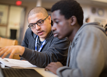 Two students looking at a laptop in discussion with each other.